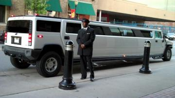Driver waiting for his guests next to the white Hummer Limousine.
